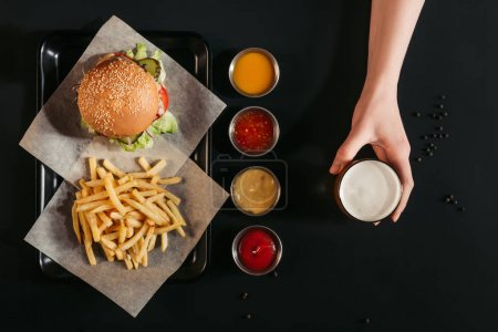 Photo for Top view of french fries with delicious burger on tray, assorted sauces and hand holding glass of beer on black - Royalty Free Image