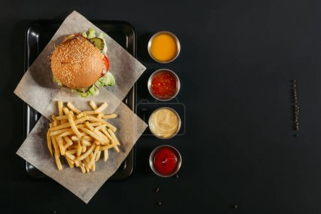 Photo for Top view of french fries with delicious burger on tray and assorted sauces on black - Royalty Free Image