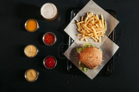 Photo for Top view of french fries and tasty burger on tray, glass of beer and assorted sauces on black - Royalty Free Image