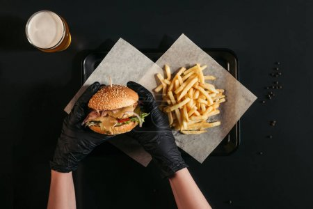Photo for Cropped shot of person in gloves holding tasty burger above tray with french fries and glass of beer on black - Royalty Free Image