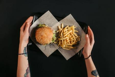 Photo for Cropped shot of human hands holding tray with delicious burger and french fries on black - Royalty Free Image