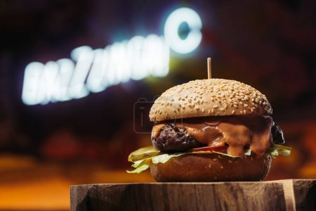 close-up view of delicious beef burger on wooden stump
