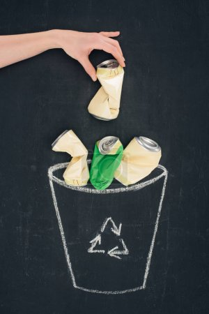 Photo pour Plan recadré de femme jetant la boîte en métal dans la poubelle tirée avec le signe de recyclage sur le tableau noir - image libre de droit
