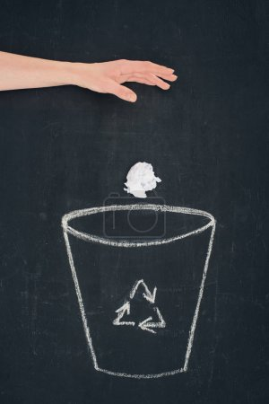 cropped shot of woman throwing crumpled paper into drawn trash bin with recycle sign on chalkboard