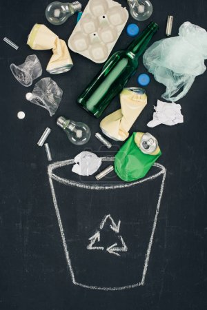 various types of trash falling into drawn trash can with recycle sign on chalkboard
