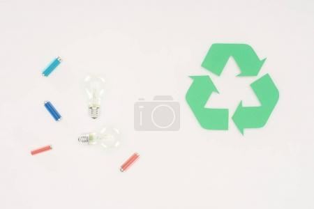 top view of light bulbs and batteries with recycle sign on white