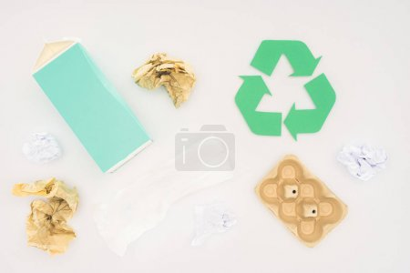 top view of various paper trash with recycle sign on white