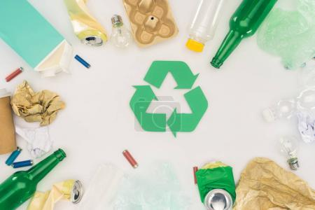 Photo for Top view of various types of trash surrounding recycle sign on white - Royalty Free Image