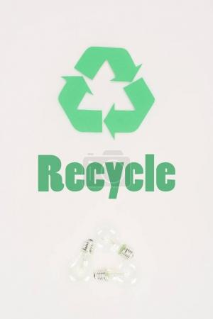 top view of light bulbs with recycle sign on white