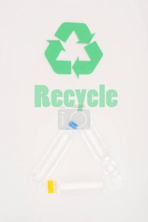 top view of plastic bottles with recycle sign on white
