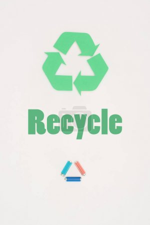 top view of batteries with recycle sign on white