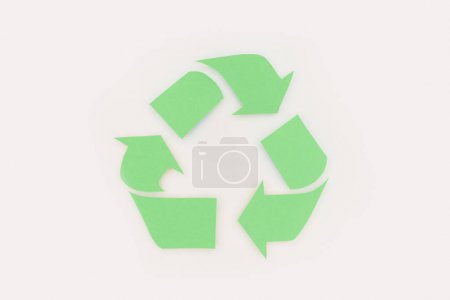 top view of green arrows recycle sign on white