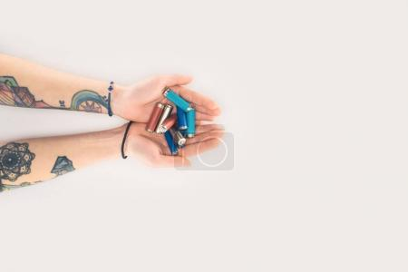 cropped shot of woman holding batteries in hands isolated on white