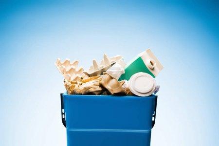 Photo pour Divers déchets de papier dans la poubelle sur bleu - image libre de droit