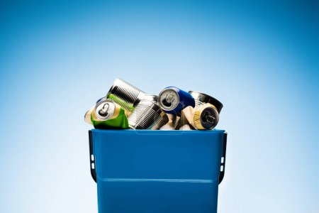 various metal cans in trash bin on blue