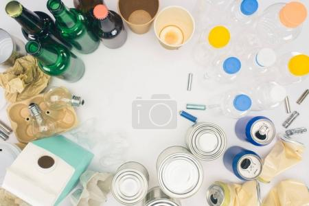 top view of round frame of different types of trash on white