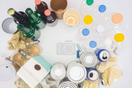 top view of round frame of various types of trash on white