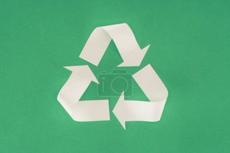 top view of white arrows recycle sign on green