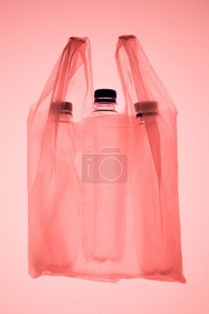 transparent plastic bag with plastic bottles under pastel pink toned light