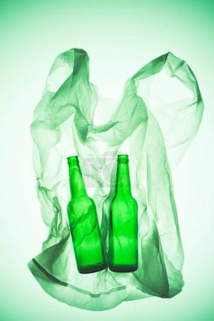 crumpled plastic bag with glass bottles under green toned light
