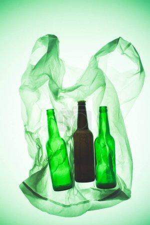 transparent plastic bag with glass bottles under green toned light