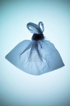 tied transparent plastic bag under blue toned light