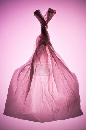 tied transparent plastic bag under pink toned light