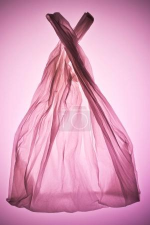 crumpled transparent plastic bag under pink toned light