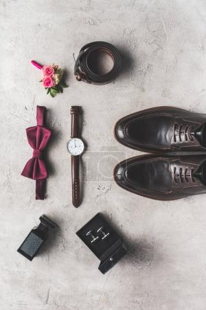 top view of bow tie, boutonniere, wristwatch and shoes for wedding on gray surface
