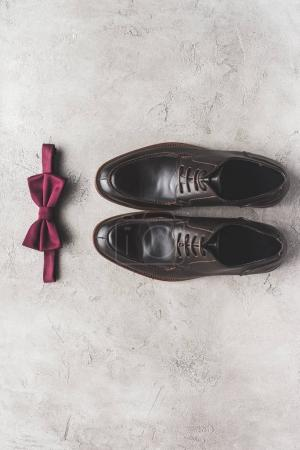 top view of pair of shoes and bow tie for wedding on gray surface