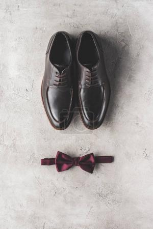 top view of pair of black wedding shoes and bow tie on gray surface