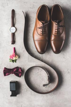 elevated view of male wedding accessories for groom on gray surface
