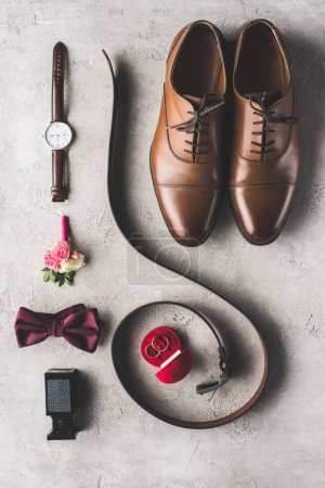 flat lay of male wedding accessories for groom on gray surface