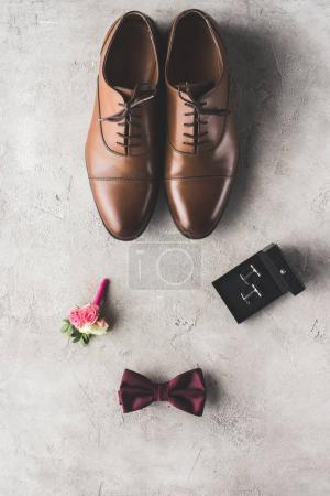 top view of brown shoes, cufflinks, bow tie and boutonniere on gray surface