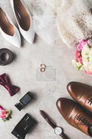 top view of wedding accessories and rings on gray tabletop