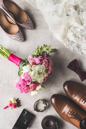 top view of wedding accessories and bouquet on gray surface