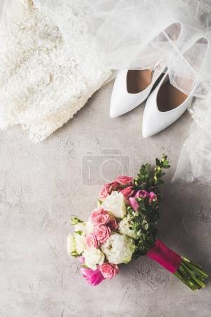 Draufsicht auf Brautkleid, Schuhe und Strauß auf grauer Oberfläche