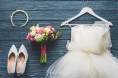 top view of wedding bouquet and dress on wooden dark blue tabletop