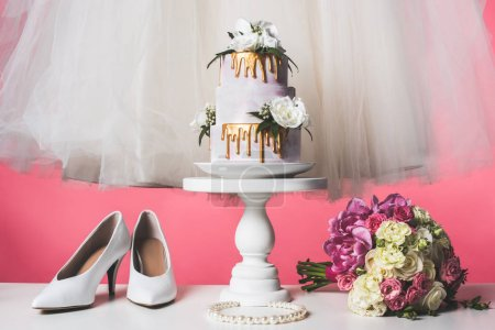 pair of shoes, wedding bouquet and white dress isolated on pink