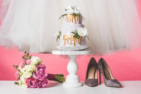 pair of shoes, wedding bouquet, cake and white dress isolated on pink