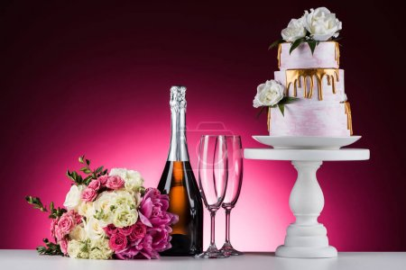 wedding bouquet, champagne with glasses and cake on stand on pink