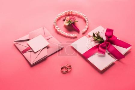 Photo for Wedding rings, pearl necklace, boutonniere and pink envelopes with invitations on pink surface - Royalty Free Image