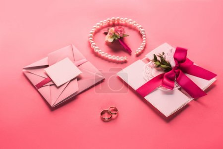 wedding rings, pearl necklace, boutonniere and pink envelopes with invitations on pink surface