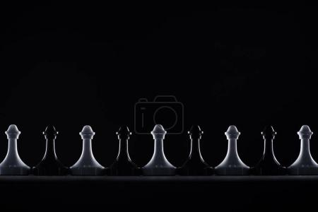 Photo for Silhouettes of black and white chess pawns isolated on black, business concept - Royalty Free Image