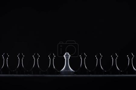 silhouettes of black and white chess pawns isolated on black, business concept