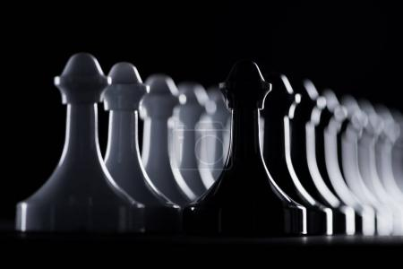 rows of white and black chess figures isolated on black, business concept