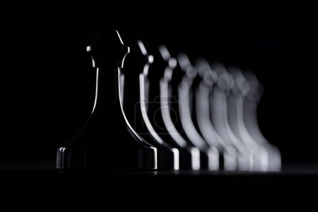 silhouettes of row of chess figures isolated on black, business concept