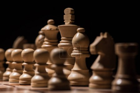 ordered white wooden chess figures on chessboard isolated on black, business concept