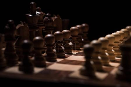 ordered chess figures on chessboard isolated on black, business concept