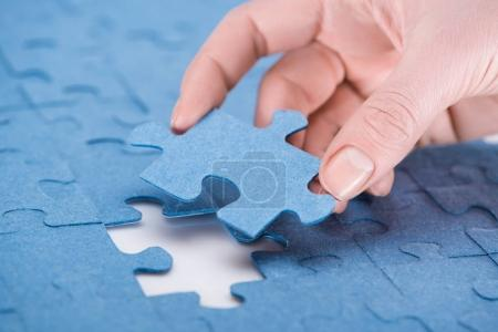 cropped image of businesswoman inserting last missing puzzle, business concept